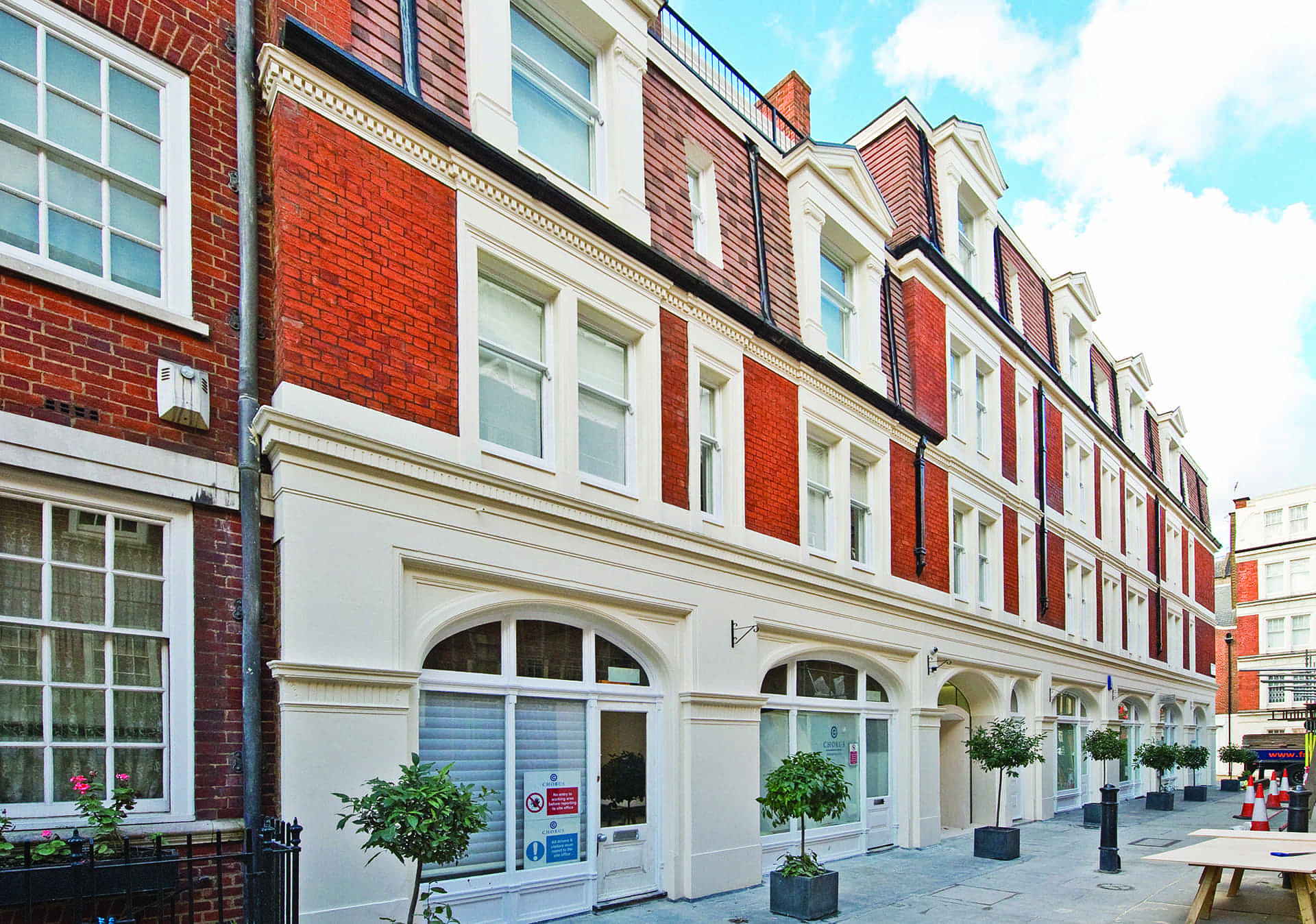 image of the red brick-layered mayfair building in London with arcade shaped windows